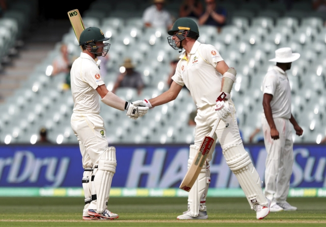 Australia's Travis Head, left, is congratulated by teammate Pat Cummins after scoring a half century during the first cricket Test between Australia and India in Adelaide.