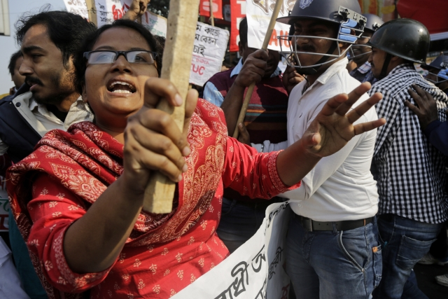 Trade union activists shout slogans as they clash with police on the first day of a two-day general strike called by various trade unions in Kolkata.