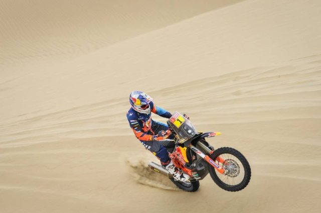 The front wheel of a bike pops as the rider tries to control through the sand.