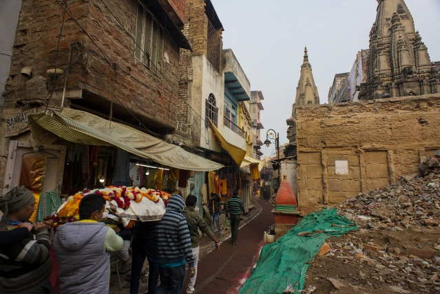 People carry a corpse to Manikarnika Ghat along a path at the demolition site.
