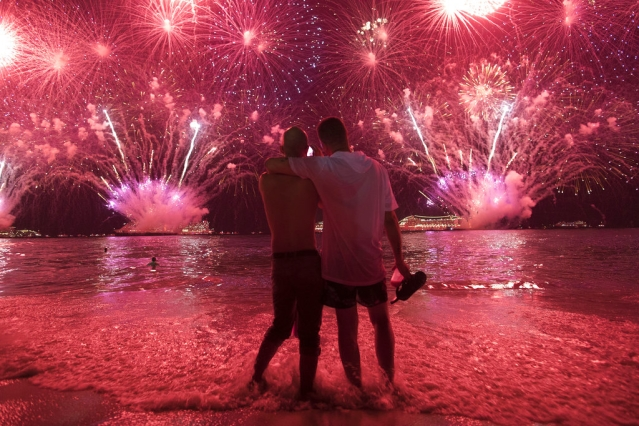 Two men watch the fireworks exploding over Copacabana Beach during the New Year's celebrations in Rio de Janeiro, Brazil, on Tuesday, 1 January 2019.