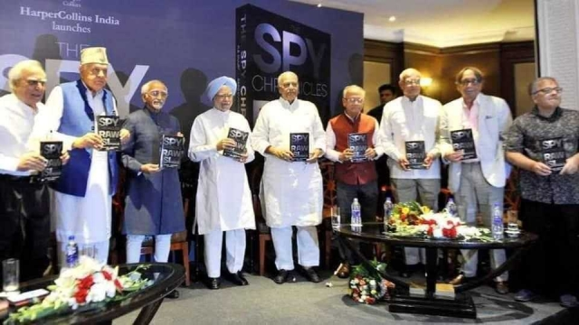 The image shows Manmohan Singh and Hamid Ansari at the book launch.