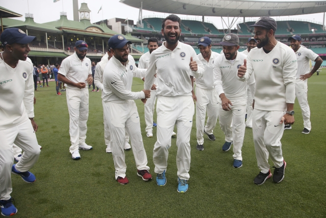 India's Virat Kohli, right, encourages Cheteshwar Pujara, center, as the team dance as they celebrate their series win over Australia after play was called off on day 5 of their cricket test match in Sydney, Monday, Jan. 7, 2019. The match is a draw and India wins the series 2-1.