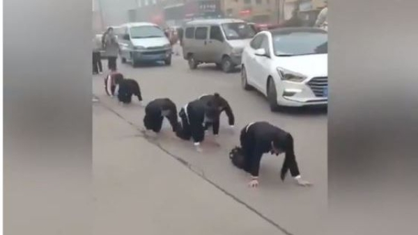 Chinese employees forced to crawl on street as punishment.