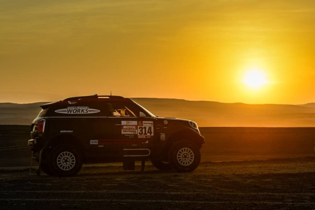 The sun sets over the desert of Pisco as an off road Mini driver passes by.