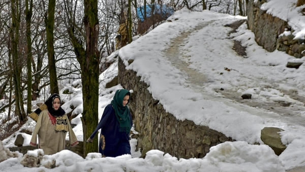 People walk on snow-covered path, on the outskirts of Srinagar.