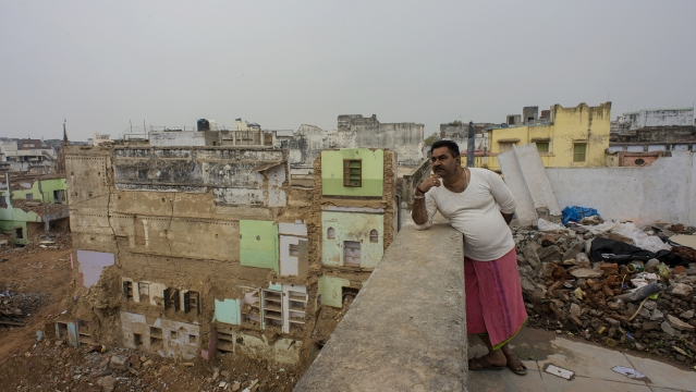 Jai Prakash Sharma leans on the parapet of the terrace of his house that he is about to vacate soon.