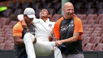 Prithvi Shaw is carried by support staff after rolling his ankle while attempting a catch during India's tour game against Cricket Australia XI in Sydney.