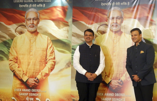 Maharashtra Chief Minister Devendra Fadnavis (left) and Bollywood actor Vivek Oberoi pose for photographs in front of posters of upcoming film <i>PM Narendra Modi</i>, a biopic on the prime minister, during its poster launch in Mumbai on Monday, 7 January, 2019.&nbsp;