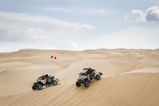Two 4x4's take on a dune in the deserts of Peru.