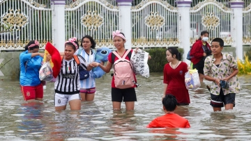 Thai people wade through floodwaters from Tropical Storm Pabuk on Friday, 4 January in the southern province of Nakhon Si Thammarat in southern Thailand.
