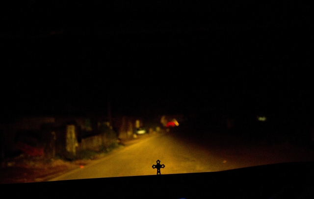 In this Thursday, 8 November, 2018, photo, a person drives in the night as a crucifix is seen on the dashboard in Kottayam