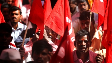 Trade union members hold flags as they participate in a demonstration on the first day of a two-day general strike called by various trade unions in Mumbai, India.
