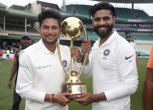 India's Kuldeep Yadav, left, and Ravindra Jadeja hold the Border-Gavaskar Trophy as they celebrate their series win over Australia after play was called off on day 5 of their cricket test match in Sydney, Monday, Jan. 7, 2019. The match is a draw and India wins the series 2-1.