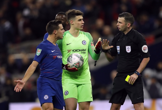 Chelsea's Cesar Azpilicueta, left, argues as Referee Michael Oliver, right, gives a yellow card to Chelsea's goalkeeper Kepa Arrizabalaga, after a video review.