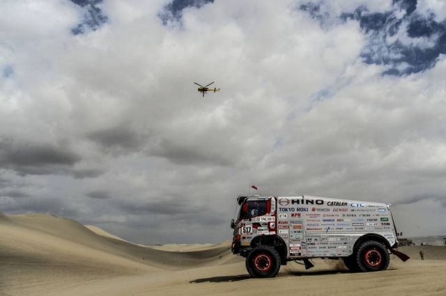 A truck during the race, as a rescue helicopter looks on.