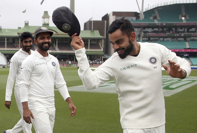 India's Virat Kohli, right, tips his hat as he celebrate with teammates their series win over Australia after play was called off on day 5 of their cricket test match in Sydney, Monday, Jan. 7, 2019. The match is a draw and India wins the series 2-1.
