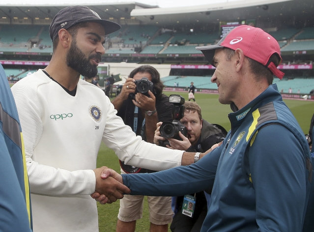 India's captain Virat Kohli, left, shakes hands with Australia's coach Justin Langer after India's series win after play was called off on day 5 of their cricket test match in Sydney, Monday, Jan. 7, 2019. The match is a draw and India wins the series 2-1.