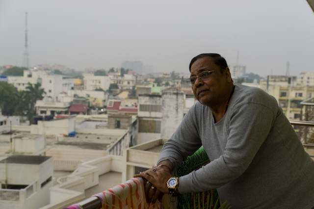 Padampati Sharma stands at the balcony of his new apartment at Mehmoorganj, some four kilometres away from his ancestral home.