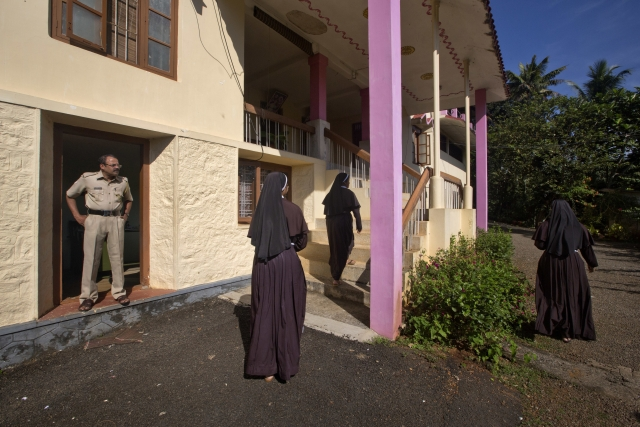 In this Sunday, 4 November, 2018, photo, a policeman stands guard as nuns who have supported the accusation of rape against Bishop Franco Mulakkal return from the chapel in St. Francis Mission Home in Kuravilangad.