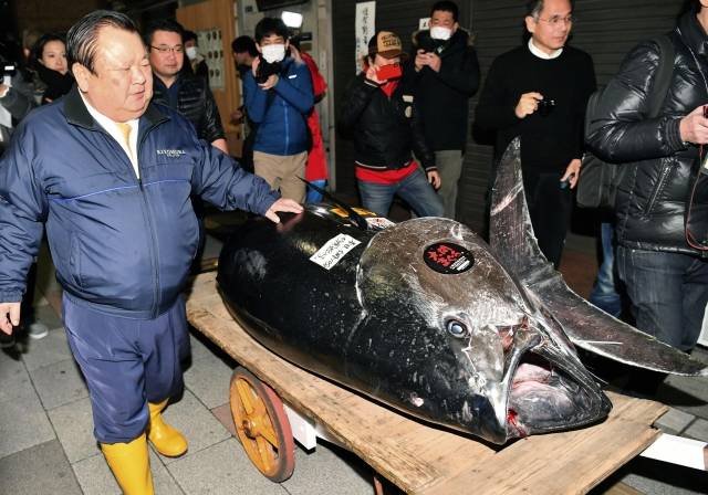 Kiyomura Corp. Owner Kiyoshi Kimura (left) stands near the bluefin tuna for which he made a wining bid at the annual New Year auction.