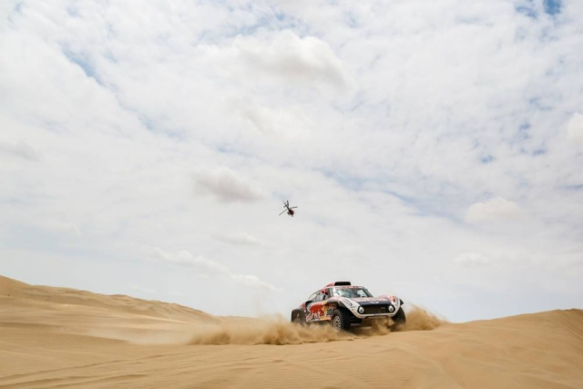 A Red Bull car struggles in the thick sand as a chopper flies by above.