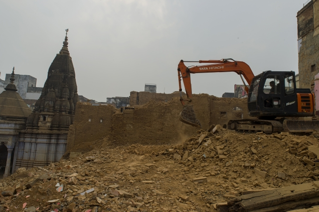 A temple stands in the background as the rubble is being cleared.
