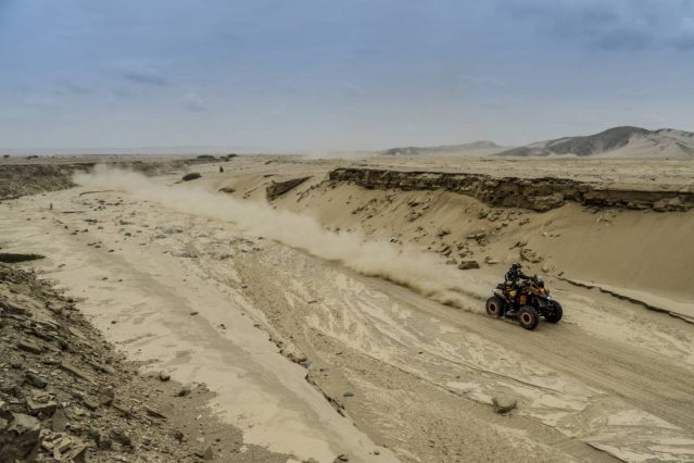A quadbike races through the deserts.