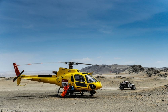 A rescue helicopter sits as a 4x4 is seen passing in the background.