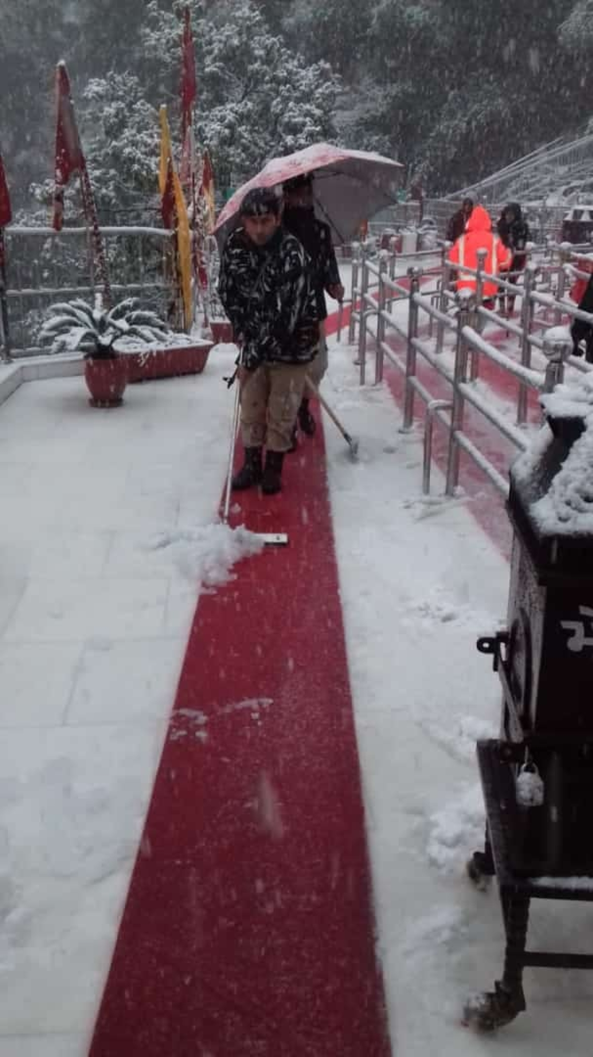 A security personnel tries to move the snow off the path to the temple in Katra.