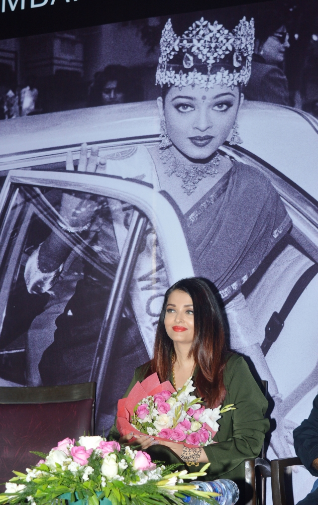 Aishwarya Rai sitting before a blown up archive photograph of her after her Miss World win in 1994.