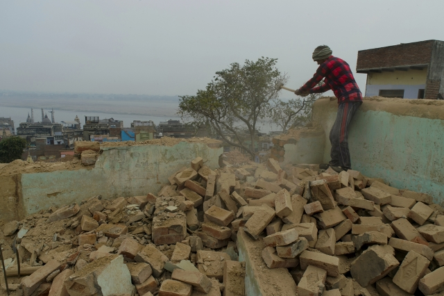 A worker breaks the parapet of a house. The Ganges is visible in the backdrop.