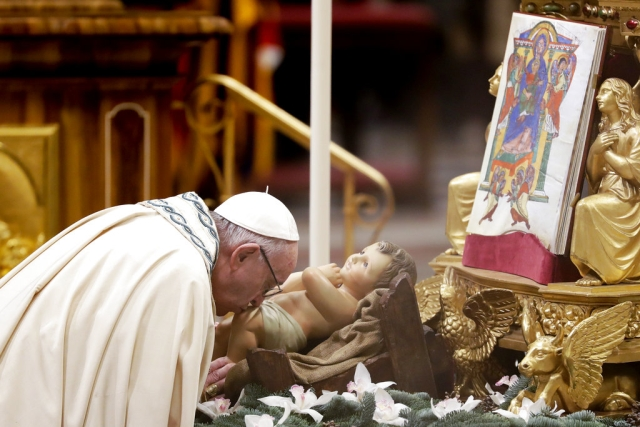 Pope Francis kisses a statue of Baby Jesus as he celebrates a new year's eve vespers Mass in St. Peter's Basilica at the Vatican, on Monday, 31 December 2018.