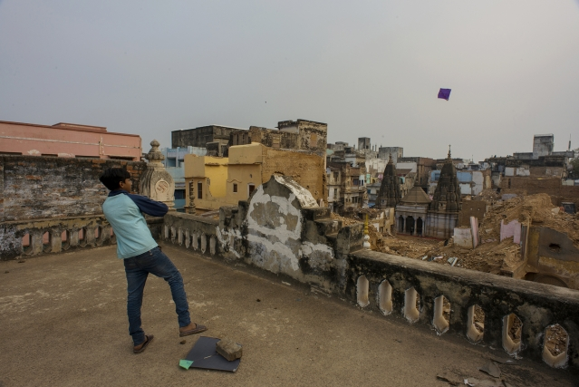A boy flies a kite from atop a house at the area marked for the project.