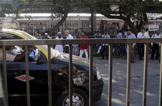 People wait in a queue for taxis on the first day of a two-day long nationwide strike in Mumbai on Tuesday, 8 January.