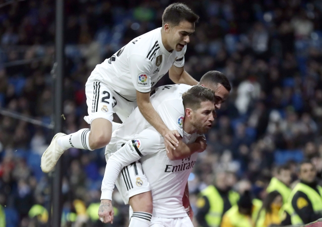 Real Madrid's Sergio Ramos, bottom, celebrates with teammates after scoring a penalty during a Spanish Copa del Rey soccer match.