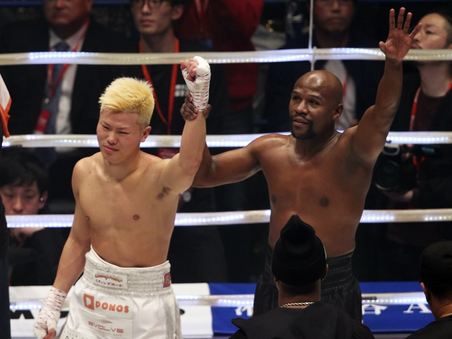 Floyd Mayweather Jr., right, holds the hand of Japanese kickboxer Tenshin Nasukawa, after beating him in their three-round exhibition match on New Year's Eve.