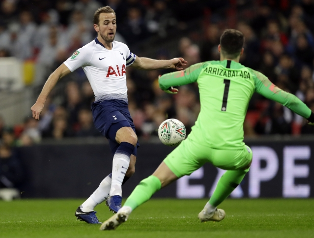 Tottenham's Harry Kane, left, faces Chelsea's goalkeeper Kepa Arrizabalaga during the English League Cup semi-final first leg soccer match.