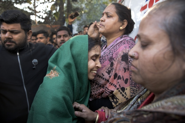 Unidentified relatives gather outside after an early morning fire at a hotel in the Karol Bagh.
