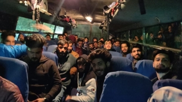 Stranded Kashmiris heading back home in a bus arranged by Khalsa Aid.