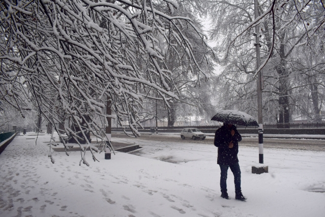 A man walks amid heavy snowfall in Srinagar.