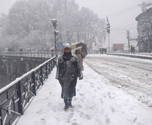 A man walks in a snowstorm in Srinagar.