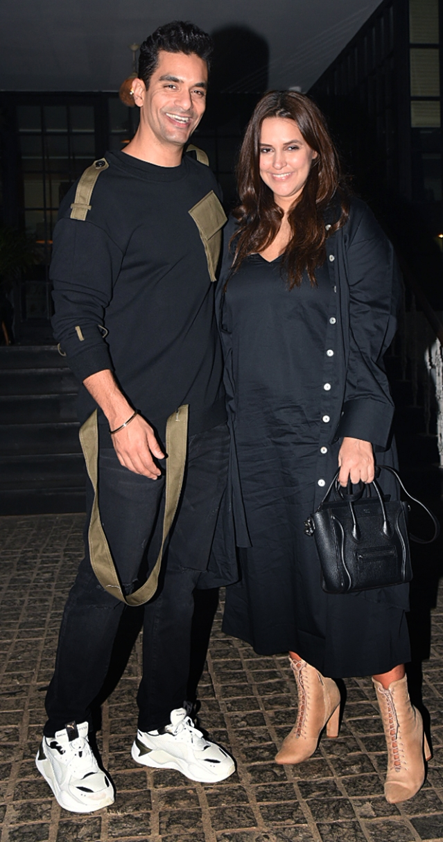 Angad Bedi and Neha Dhupia pose for the camera.