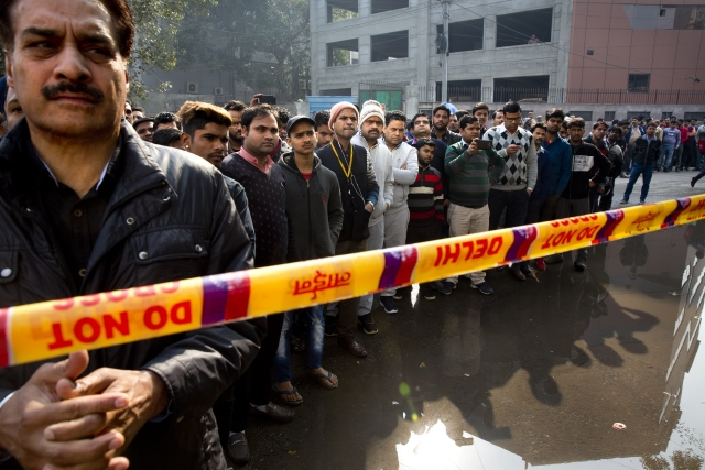 Onlookers gather after an early morning fire at a hotel killed at least 17 people in the Karol Bagh area of New Delhi.
