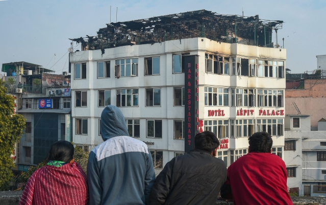 People look on at Karol Bagh's Hotel Arpit Palace where a massive fire broke out, in New Delhi on Tuesday, 12 February. At least 17 people were killed and several others were injured in the accident.