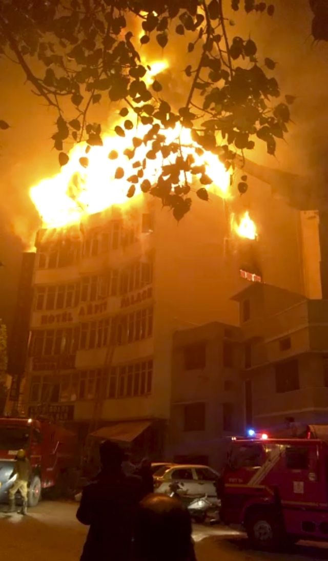 In this frame grab provided by Shyamal Duary, flames rise from a hotel that caught fire in the early hours of the morning in New Delhi on Tuesday. The fire engulfed a shoddily built budget hotel, killing 17 people and injuring at least four others, including a woman from Myanmar who leaped from an upper floor to escape the flames, officials told AP.