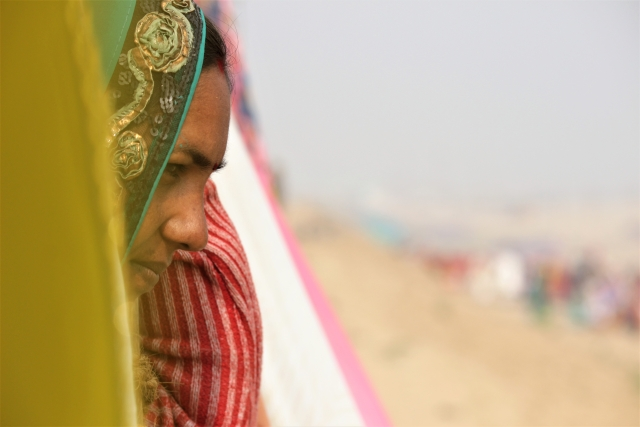 Natthi stares at the river, through the pile of clothes, left on bamboo shafts to dry,