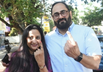 Bengaluru: BJP Rajya Sabha MP Rajeev Chandrasekhar along with his wife Anju Chandrasekhar shows their finger marked with phosphoric ink after casting their vote at a polling booth during Karnataka Assembly Polls at Koramangala Assembly Constituency, in Bengaluru on May 12, 2018. (Photo: IANS)