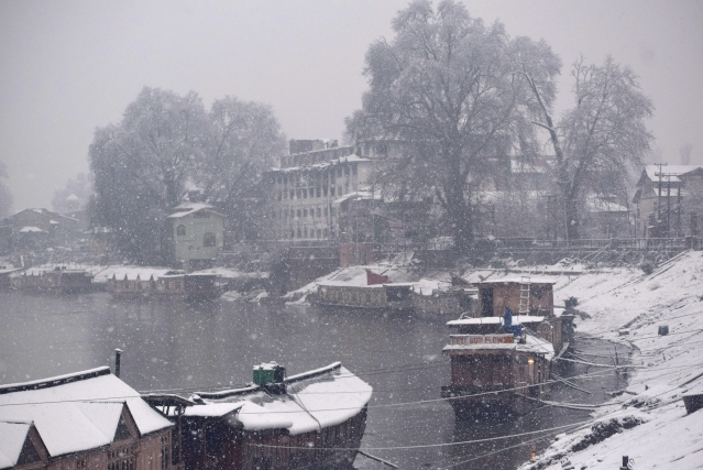 A man clears snow from roof top of houseboat at Jehlum river in Srinagar.