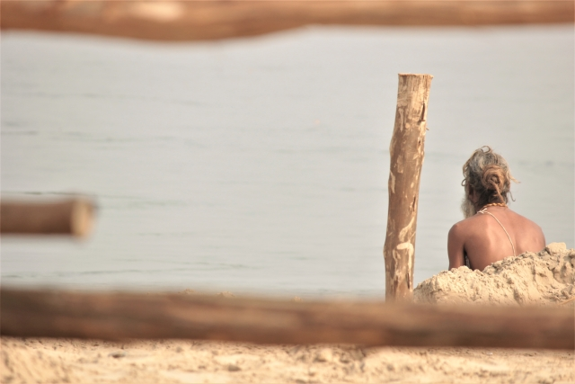 A Sadhu sitting by the banks of a river.